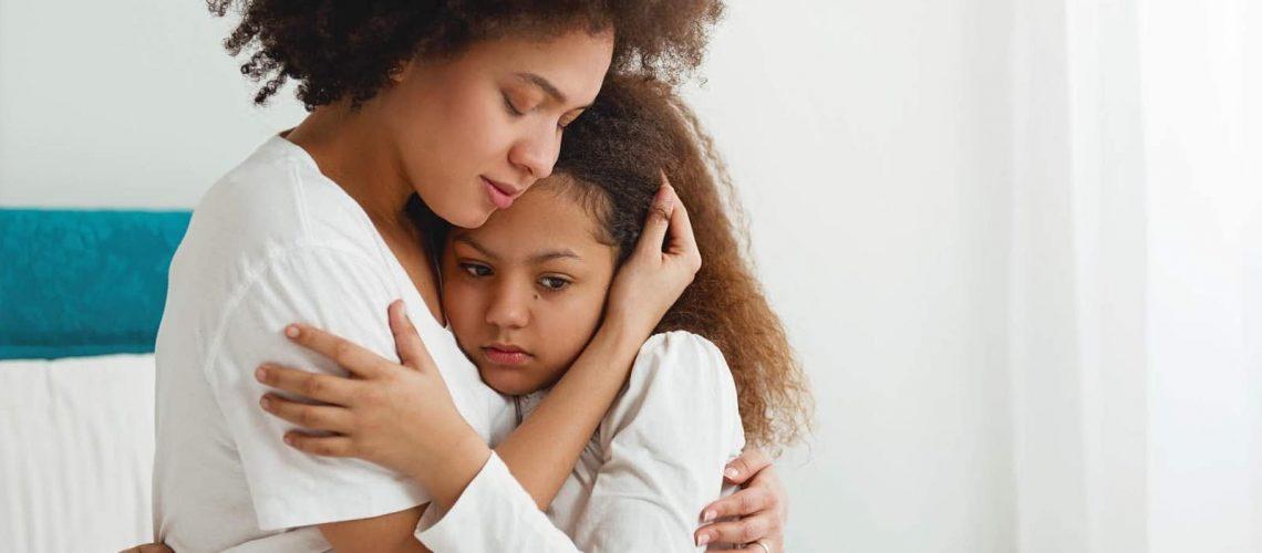 Mother comforting her daughter, sitting in the bedroom, hugging